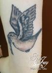 black and grey traditional bird tattoo