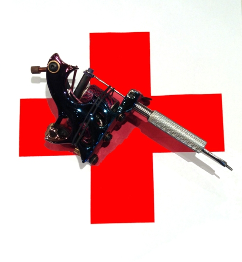 red cross with tattoo machine