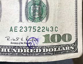 211 stamp in circle on 100 bill