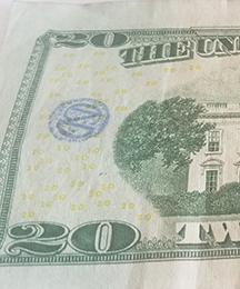 CND monogram stamp on $20